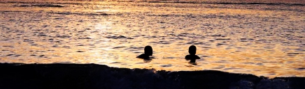 people-swimming-at-the-beach-sunset-header