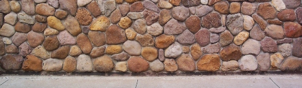 concret-floor-and-brown-pebbles-stones-wall-header