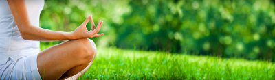 yoga-girl-meditating-pose-in-green-grass-field-web-header