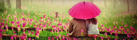 cute-couple-with-umbrella-in-blossom-field-header_size-1024x300