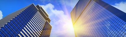 blue-modern-glass-buildings-sun-rays-web-header_size-1024x300